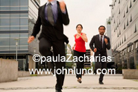 A group of three multi-ethnic business people or executives running between office buildings. One woman two men.
